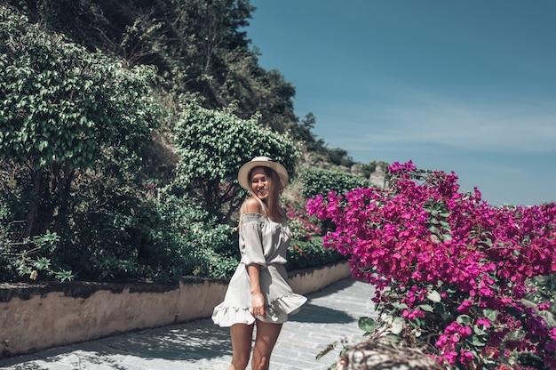 De mooie opgewekte blondevrouw loopt en bewondert tropische landschappen bij het hotel van het paradijseiland in sanya, china.