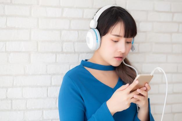 De mooie portret aziatische jonge vrouw luistert muziek