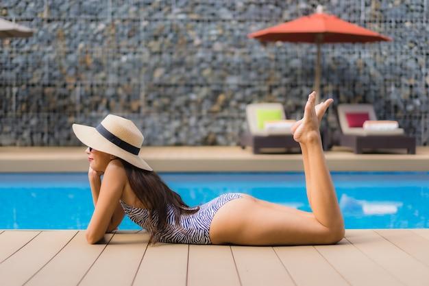 De mooie portret aziatische vrouw ontspant gelukkige glimlach rond openlucht zwembad