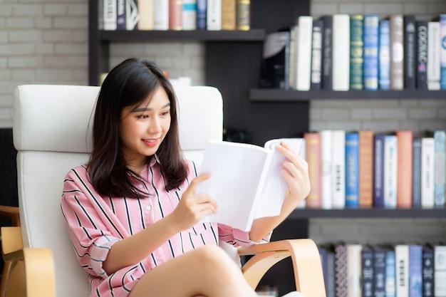 De mooie portret aziatische vrouw ontspant het boek van de zittingslezing