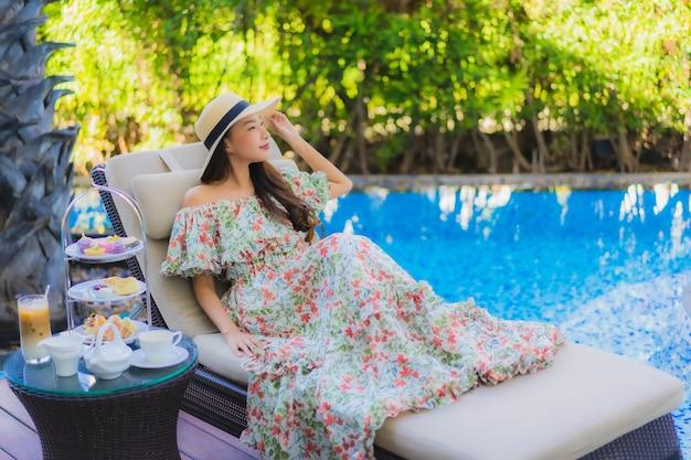 De mooie portret jonge aziatische vrouw met middagmiddeltheestel met koffie zit op stoel rond zwembad