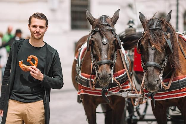 De mooie pretzel van de jonge mensenholding naast paarden