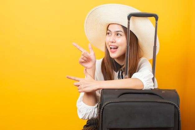 De mooie reizigersvrouw is opwindend op geel