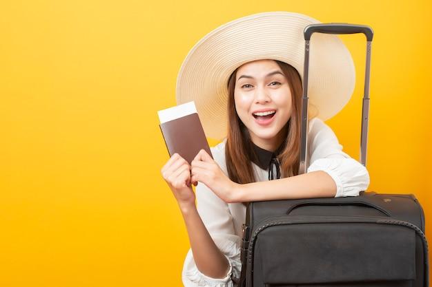 De mooie reizigersvrouw is opwindend op gele muur