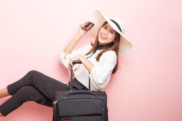 De mooie reizigersvrouw is opwindend op roze achtergrond