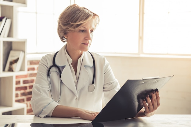 De mooie rijpe arts in witte laag bestudeert documenten.