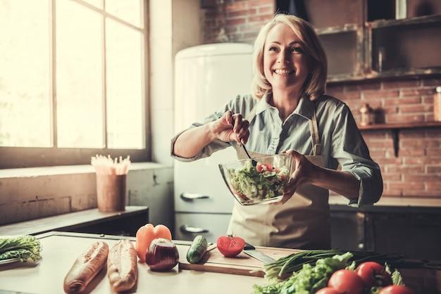 De mooie rijpe vrouw in schort mengt salade.