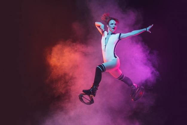 De mooie roodharigevrouw in een rode sportkleding die in een kangoo springen springt schoenen op donkere studioachtergrond.