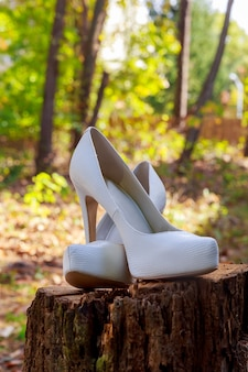 De mooie schoenen van de bruid met bloemen aan de zijkant.