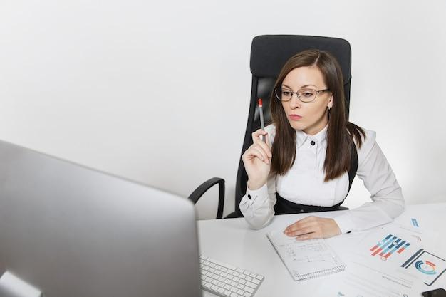 De mooie serieuze en verdiepte bruinharige zakenvrouw in pak en bril zit aan het bureau, werkend op de computer met moderne monitor met documenten in een licht kantoor,