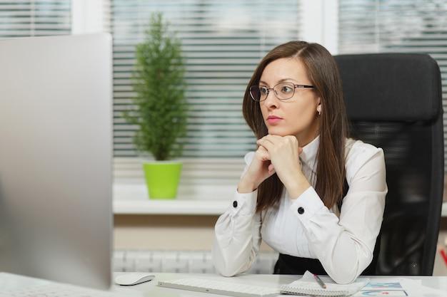 De mooie serieuze en verdiepte bruinharige zakenvrouw in pak en bril zittend aan het bureau met tablet, werken op computer met moderne monitor met documenten in licht kantoor, opzij kijkend