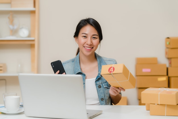 De mooie slimme aziatische jonge ondernemer van de ondernemers bedrijfsvrouw van kmo die product op qr van het voorraadaftasten code controleren die thuis werken.