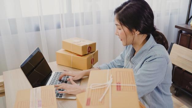 De mooie slimme aziatische jonge ondernemer van de ondernemers bedrijfsvrouw van online het controleren van het mkb product