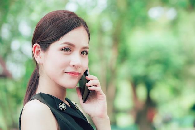 De mooie slimme zaken zien eruit aziatische vrouw die met slimme telefoon in het park roept