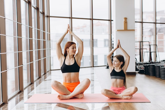 De mooie spiervrouw en haar charmant dochtertje glimlachen terwijl samen het doen van yoga bij gymnastiek