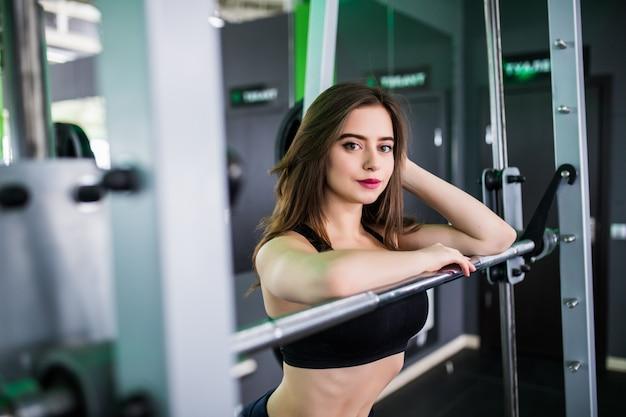De mooie sterke glimlachende dame met barbell stelt in sportclub
