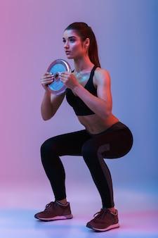 De mooie sterke jonge sportenvrouw maakt oefeningen