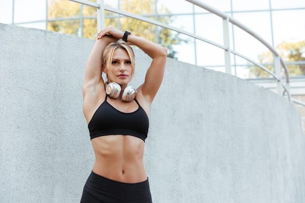 De mooie sterke jonge sportenvrouw maakt sportoefeningen