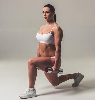 De mooie sterke vrouw in wit ondergoed doet lunges.