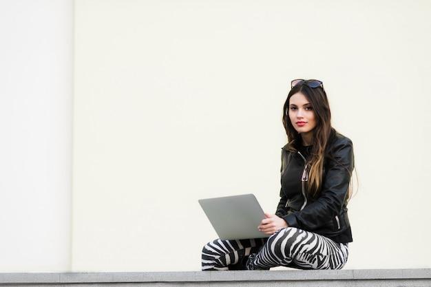 De mooie studentenvrouw glimlacht gebruikend laptop en zit op oude muur in de universitaire campus. schitterende vrouw die met computer in openlucht bij universiteitspark werkt.