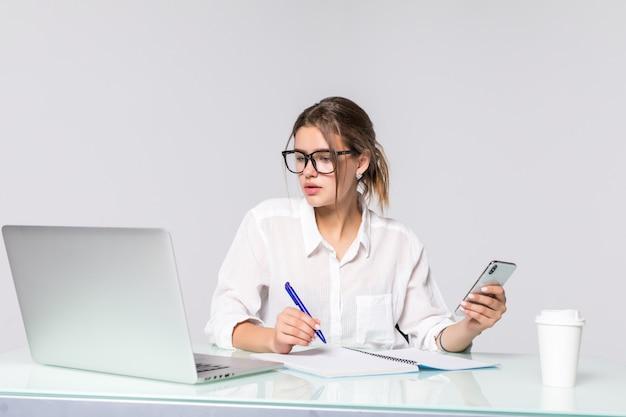 De mooie telefoon van de bedrijfsvrouwenholding met de computer op kantoor dat op witte achtergrond wordt geïsoleerd