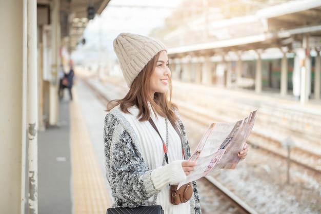 De mooie toeristenvrouw bevindt zich op spoorwegplatform met haar kaart