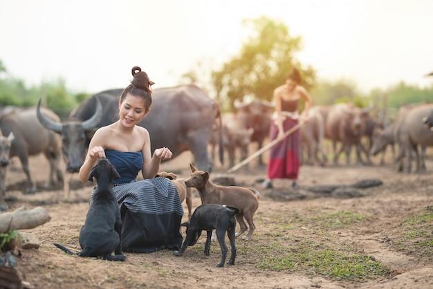 De mooie twee aziatische vrouwen kleedden zich in traditioneel kostuum met buffels bij landbouwgrond, één zit op begane grondspel met honden en één gebruik spade graaft grond.