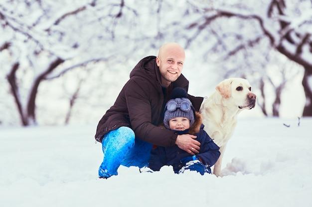 De mooie vader, zoon en hond zitten in de sneeuw