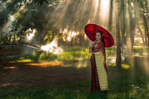 De mooie van de de holdingshand van het vrouwen thaise meisje jasmijnslinger in traditioneel thais kostuum met tempelayutthaya is textuurgoud, identiteitscultuur van thailand.