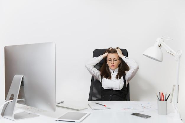 De mooie vermoeide, verwarde en stressvolle zakenvrouw met bruin haar in pak en bril zit aan het bureau, werkend op een moderne computer met documenten in een licht kantoor