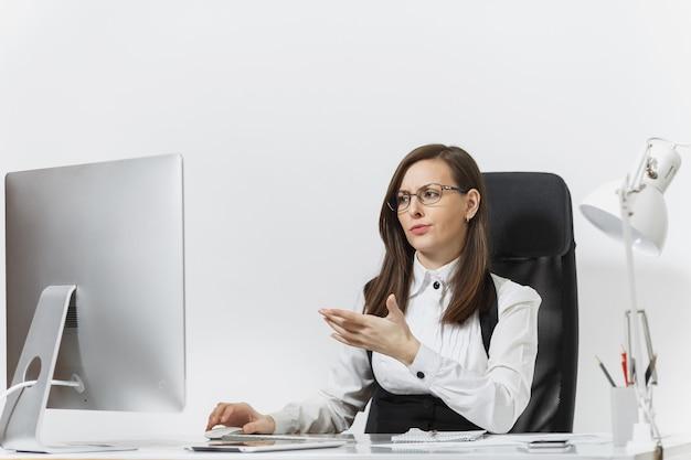 De mooie verraste en verontwaardigde bruinharige zakenvrouw in pak en bril die aan het bureau zit, werkend op de computer met moderne monitor met documenten in een licht kantoor,