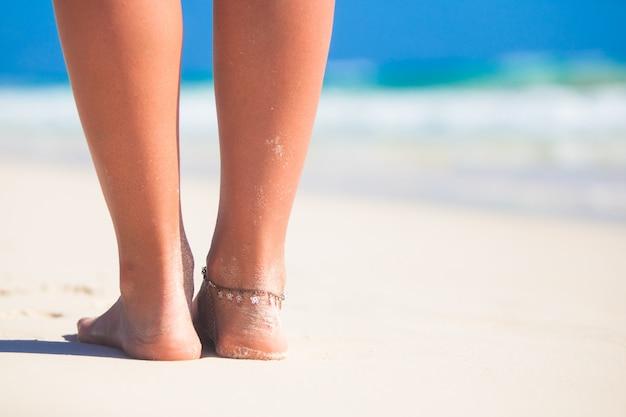 De mooie vlotte benen van vrouwen op wit zandstrand