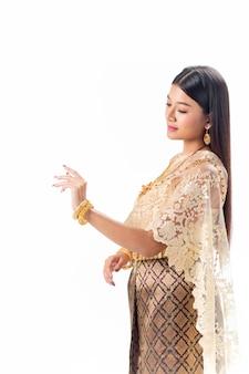 De mooie vrouw bekijkt haar indient nationaal traditioneel kostuum van thailand. isotate