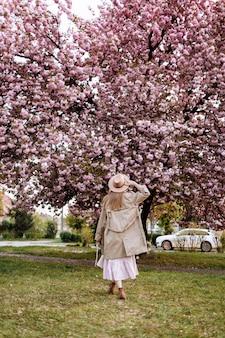 De mooie vrouw bevindt zich met haar rug dichtbij de sakurabomen. vrouw in hoed, jurk en stijlvolle jas. roze bloemen die in uzhhorod, de oekraïne bloeien. bloei rond. lente tijd concept