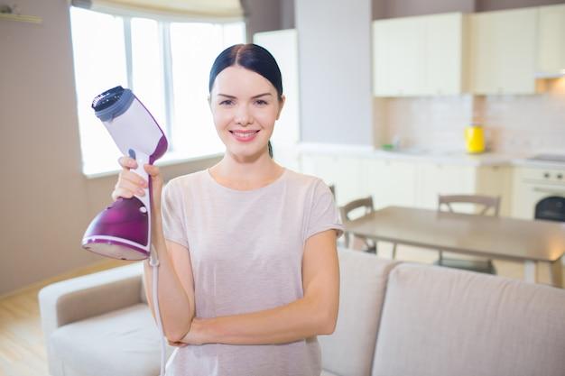 De mooie vrouw bevindt zich met kleine in hand stofzuiger en stelt op camera. ze is klaar met schoonmaken. meisje ziet er blij uit.