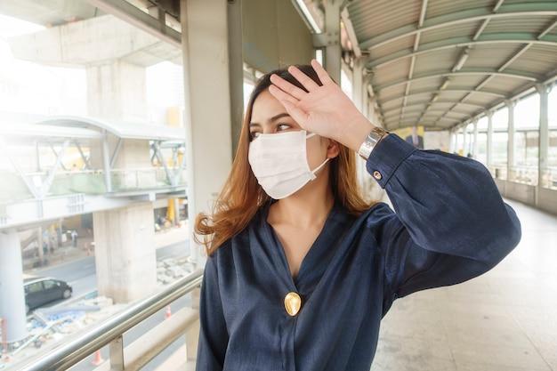 De mooie vrouw die antistofmasker draagt beschermt luchtvervuiling en pm 2.5 op straatstad