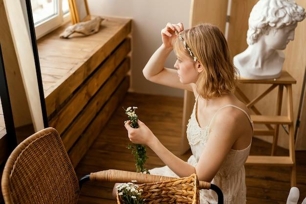 De mooie vrouw die een de lentebloemen kroon draagt
