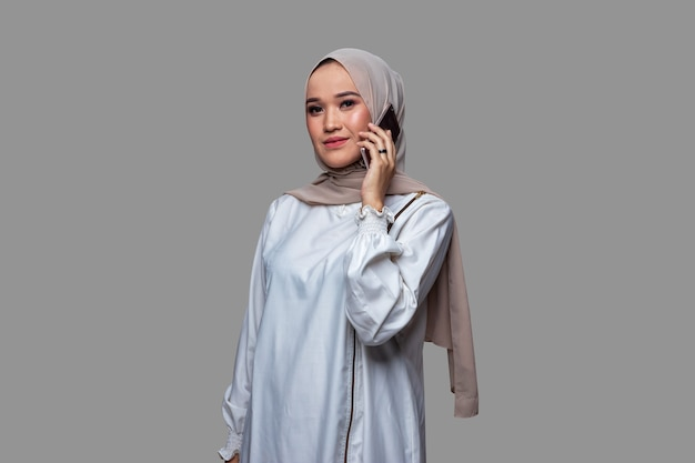 De mooie vrouw die een hijab draagt, voert een telefoongesprek met een rustige uitdrukking