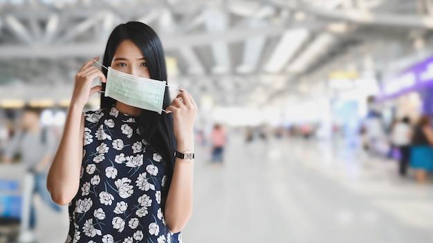 De mooie vrouw die een medisch masker dragen en zich over vage internationale airportliving bevinden met verhindert concept.