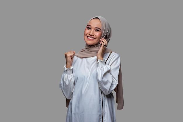 De mooie vrouw die hijab draagt, is aan het telefoneren met een succesvolle uitdrukking