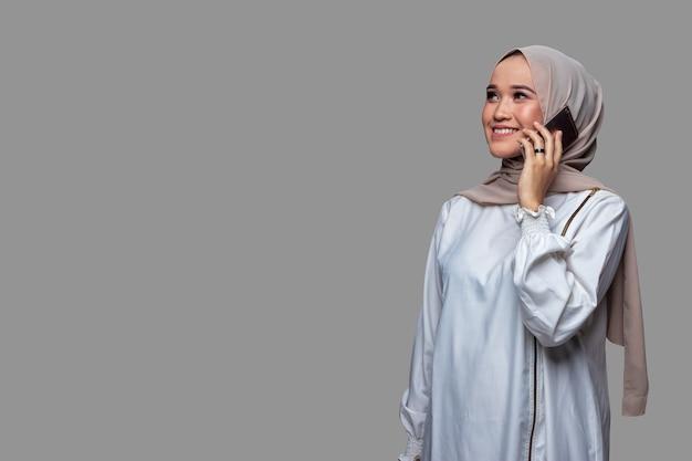 De mooie vrouw die hijab draagt, telefoneert met een glimlachende uitdrukking terwijl ze omhoog kijkt