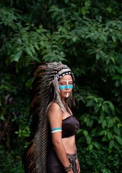 De mooie vrouw die hoofdtooiveren van vogels draagt. verf lichaam met bruine kleur en gezicht met blauwe kleur, het model stellen in bos