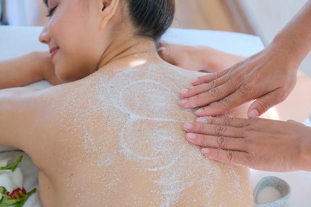 De mooie vrouw die van azië genieten van een zout schrobt massage in health spa in thailand