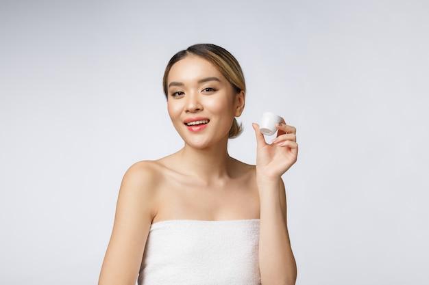 De mooie vrouw die van azië product voorstellen dat op witte achtergrond wordt geïsoleerd.