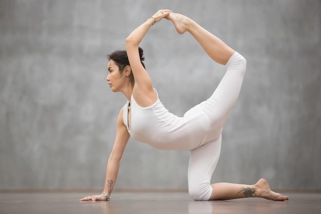De mooie vrouw die van yogi chakravakasana doet stelt