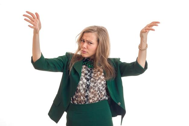De mooie vrouw die verrast draagt hief omhoog haar handen op en kijkt direct geïsoleerd op witte muur