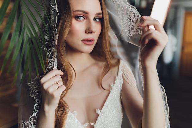 De mooie vrouw die zich in een trouwjurk.
