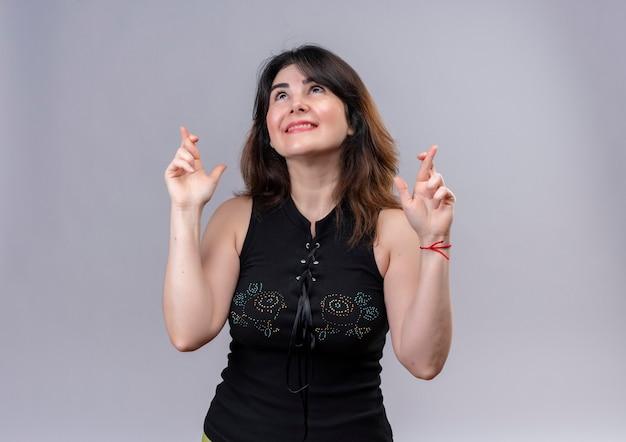 De mooie vrouw die zwarte blouse draagt die droomt verheugd kruist haar vingers over grijze achtergrond