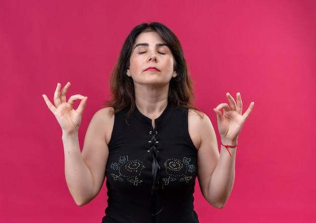 De mooie vrouw die zwarte blouse draagt mediteert