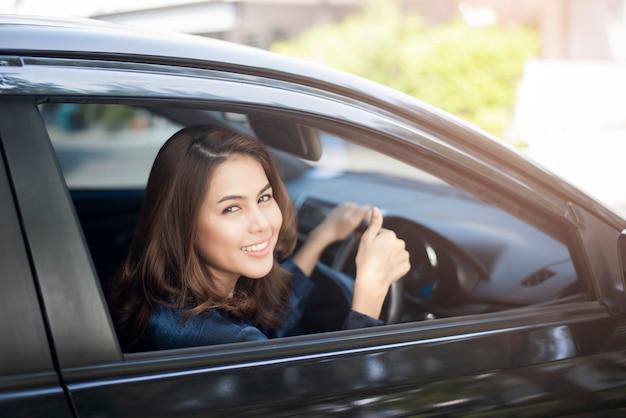 De mooie vrouw drijft haar auto